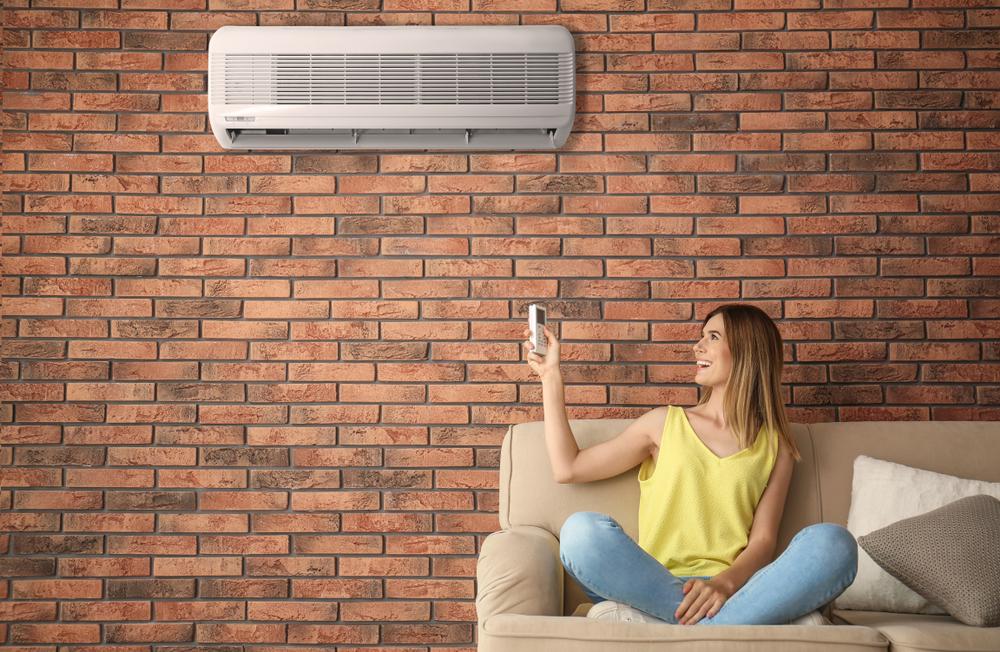 Mulher usando ar-condicionado para controlar a umidade