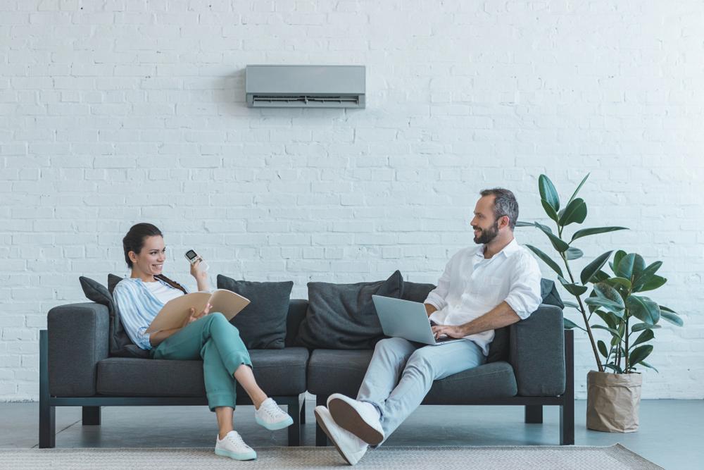 Casal conversando e usando um ar-condicionado