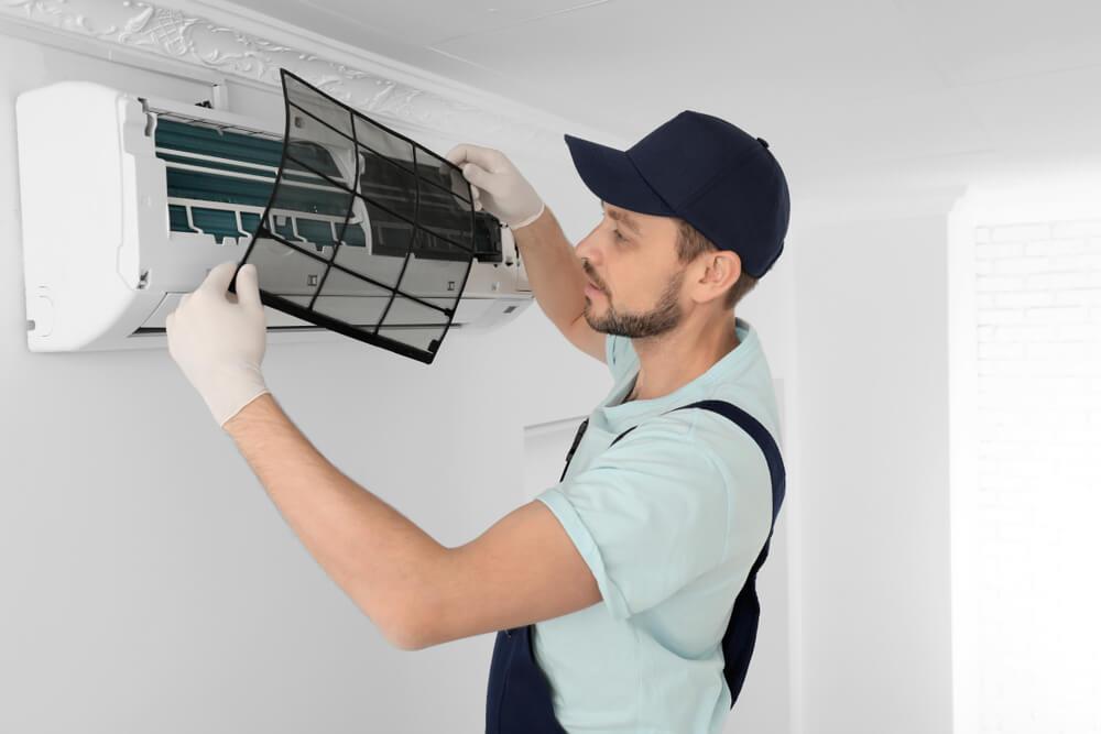 Técnico fazendo manutenção do ar-condicionado