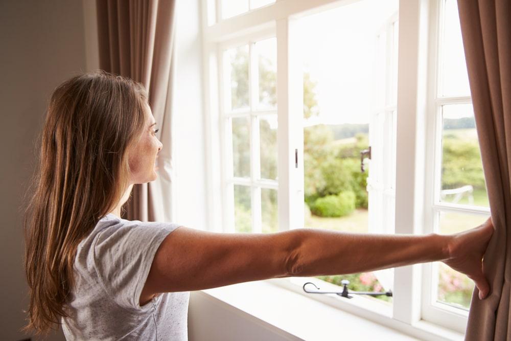 Mulher abrindo janela para deixar o ar circular, o que evita o vírus.