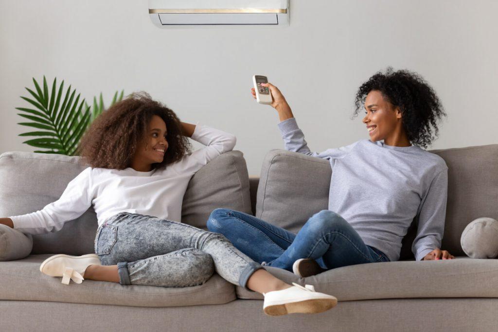 duas mulheres sentadas no sofá cinza sob o ar condicionado