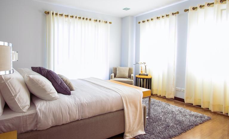 quarto com cama, poltrona, cortinas brancas e tapete