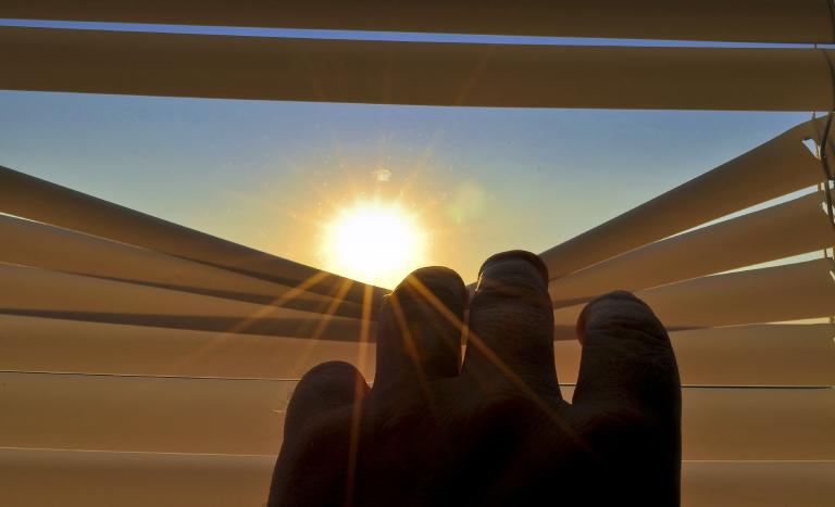 mão abrindo persiana fechada. Ao fundo, aparece o sol brilhando.