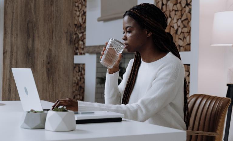 Mulher bebendo copo de água no escritório