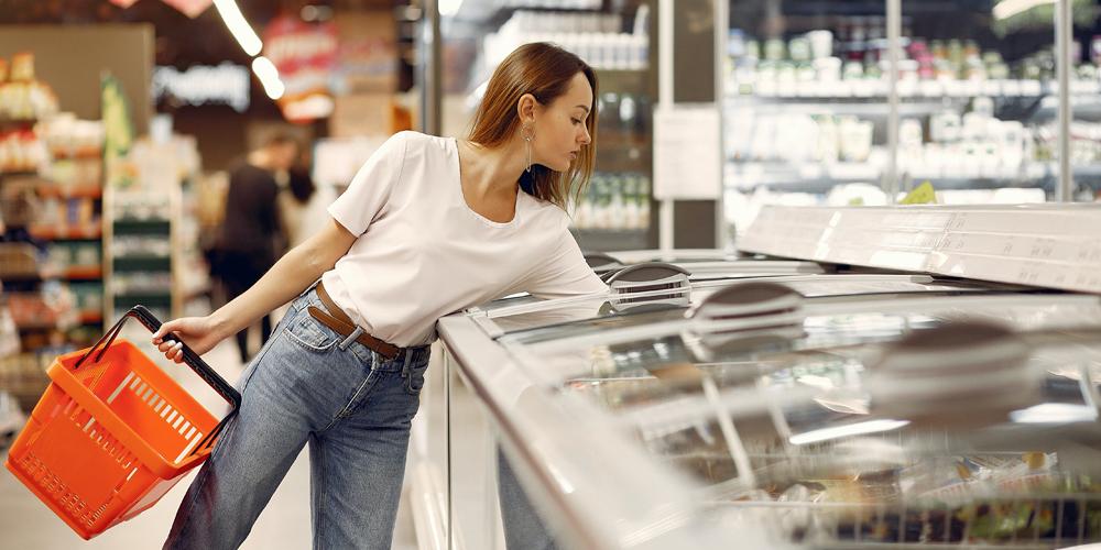 mulher usando freezer de supermercado