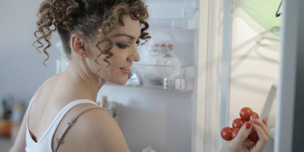 mulher com a porta da geladeira aberta