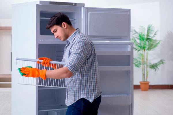 homem limpando prateleira de geladeira