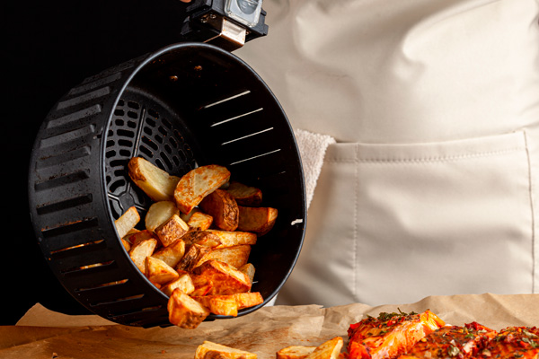 mulher fazendo batata frita na fritadeira air fryer
